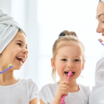 Mom brushing her teeth with kids.