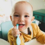 baby using a toothbrush as a teething toy.